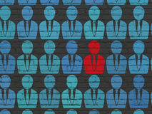 Business concept: business man icon on wall. Business concept: rows of Painted blue business man icons around red business man icon on Black Brick wall Royalty Free Stock Photography