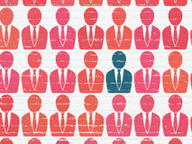 Business concept: business man icon on wall. Business concept: rows of Painted red business man icons around blue business man icon on White Brick wall Stock Photos