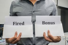 Business concept - businessman hold fired and bonus sign for work performance. Business concept - businessman hold fired and bonus sign for working performance royalty free stock photo