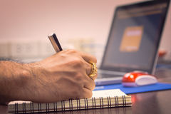 Business Concept. Businessman write note to a book on a table at office Royalty Free Stock Images