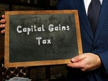 Business concept about Capital Gains Tax with sign on the black chalkboard