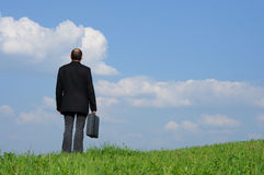 Business concept career. Businessman on hill top looking forward Stock Images