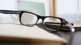 Business concept. Close up. Glasses are put on notepad. White notebook and a cup of coffee in background. Glasses, Pen
