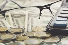 Business concept. Closeup of spectacles near money on dollar banknotes with coins and calculator Stock Photo