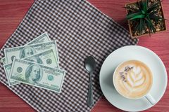 Business concept with coffee, money, cactus and fabric on pink wooden table. Copy space Stock Photography