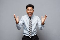 Business Concept - Confident cheerful young African American showing hands in front of him with disappointed expression. Over grey background Stock Image