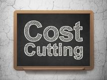Business concept: Cost Cutting on chalkboard background. Business concept: text Cost Cutting on Black chalkboard on grunge wall background, 3D rendering Royalty Free Stock Photography
