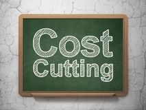Business concept: Cost Cutting on chalkboard background. Business concept: text Cost Cutting on Green chalkboard on grunge wall background, 3D rendering Stock Photo