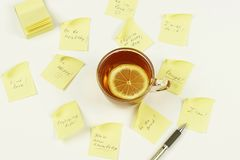 To do list and goals. Business concept. a cup of tea with lemon and colored notes to do list and goals on pale yellow background Royalty Free Stock Image
