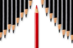 Business concept of disruption, leadership or think different; red pencil dividing row of black pencils in opposite direction royalty free stock photography