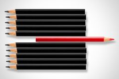 Business concept of disruption, leadership or think different; red pencil in row of black pencils pointing in opposite direction stock photography
