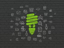 Business concept: Energy Saving Lamp on wall background. Business concept: Painted green Energy Saving Lamp icon on Black Brick wall background with  Hand Drawn Royalty Free Stock Images