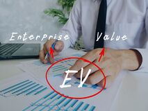Business concept about EV Enterprise Value with handwritten acronym.Busy businessman under stress due to excessive work on