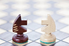 The business concept of fighting, confrontation of ideas. Chessboard and the figures of the horses. Royalty Free Stock Images