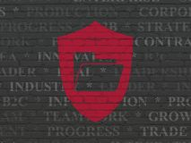 Business concept: Folder With Shield on wall background. Business concept: Painted red Folder With Shield icon on Black Brick wall background with  Tag Cloud Royalty Free Stock Photography