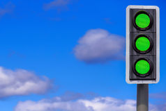 Business Concept: Full Steam Ahead/All Systems Go!. Traffic Lights Against a Blue Sky. All 3 are coloured Green indicating concepts such as Success, Full Steam Royalty Free Stock Image