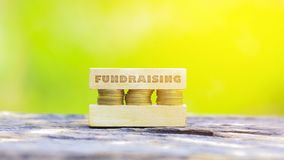 Business Concept -FUNDRAISING WORD, Golden coin stacked with woo. Business Concept - FUNDRAISING WORD, Golden coin stacked with wooden bar on shallow DOF green Royalty Free Stock Photos