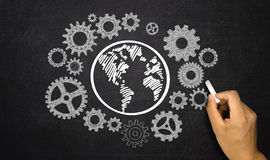 Business concept: gears around earth Stock Photos