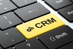 Business concept: Gears and CRM on computer. Business concept: computer keyboard with Gears icon and word CRM, selected focus on enter button, 3d render Royalty Free Stock Photography