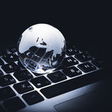 Business concept of glass globe on a laptop keyboard Royalty Free Stock Photo