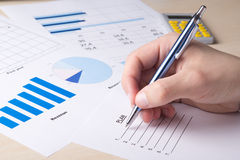Business concept - graphs and charts analyzed by businessman stock photography