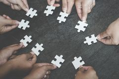 Business concept, Group of business people assembling jigsaw puzzle and represent team support and help togethe stock photography