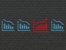 Business concept: growth graph icon on wall. Business concept: row of Painted blue decline graph icons around red growth graph icon on Black Brick wall Royalty Free Stock Photos