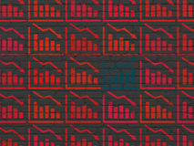 Business concept: growth graph icon on wall. Business concept: rows of Painted red decline graph icons around blue growth graph icon on Black Brick wall Royalty Free Stock Photography