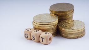 Business Concept with a GST word on stacked coins. Stock Image
