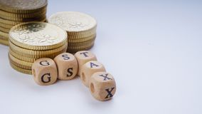 Business Concept with a GST word on stacked coins. Stock Photos