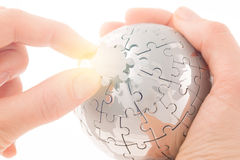 Business concept with a hand building puzzle globe royalty free stock photography