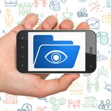 Business concept: Hand Holding Smartphone with Folder With Eye on display. Business concept: Hand Holding Smartphone with  blue Folder With Eye icon on display Stock Image