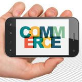 Business concept: Hand Holding Smartphone with Commerce on display. Business concept: Hand Holding Smartphone with Painted multicolor text Commerce on display stock images