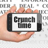Business concept: Hand Holding Smartphone with Crunch Time on display Stock Image