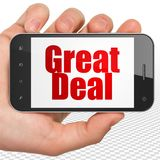 Business concept: Hand Holding Smartphone with Great Deal on display. Business concept: Hand Holding Smartphone with red text Great Deal on display, 3D rendering royalty free stock photo