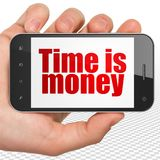Business concept: Hand Holding Smartphone with Time is Money on display. Business concept: Hand Holding Smartphone with red text Time is Money on display, 3D Stock Photography