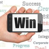 Business concept: Hand Holding Smartphone with Win on display Royalty Free Stock Photo