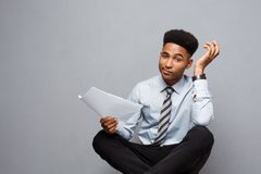 Business Concept - handsome young professional african american businessman serious reading paperworks. Royalty Free Stock Photo