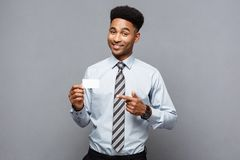 Business Concept - Happy handsome professional african american businessman showing name card to client. royalty free stock image