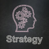 Business concept: Head With Gears and Strategy on. Business concept: Head With Gears icon and text Strategy on Black chalkboard background, 3d render Royalty Free Stock Photo