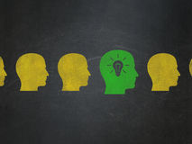 Business concept: head with light bulb icon on. Business concept: row of Painted yellow head icons around green head with light bulb icon on School Board Royalty Free Stock Photography