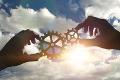 Business concept idea. two hands collect a puzzle of gears. Royalty Free Stock Image