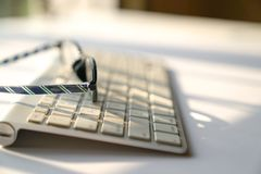 Business concept: keyboard and reading glasses on white background stock photography