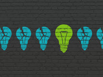 Business concept: light bulb icon on wall. Business concept: row of Painted blue light bulb icons around green light bulb icon on Black Brick wall background, 3d Stock Photography