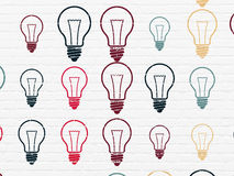 Business concept: Light Bulb icons on wall. Business concept: Painted multicolor Light Bulb icons on White Brick wall background Royalty Free Stock Images