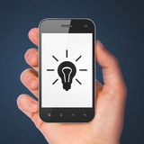 Business concept: Light Bulb on smartphone Royalty Free Stock Photos