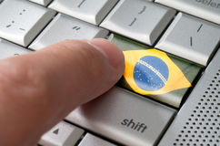 Business concept male finger pressing Brazil enter key Stock Photo
