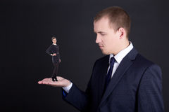 Business concept - man holding woman on his hand over grey Stock Image