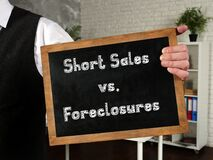 Business concept meaning Short Sales vs. Foreclosures with sign on the sheet