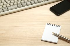 Business concept.  Memo pad, smart phone, with computer keyboard and pen.  Workplace for the business person. Business concept Royalty Free Stock Photography